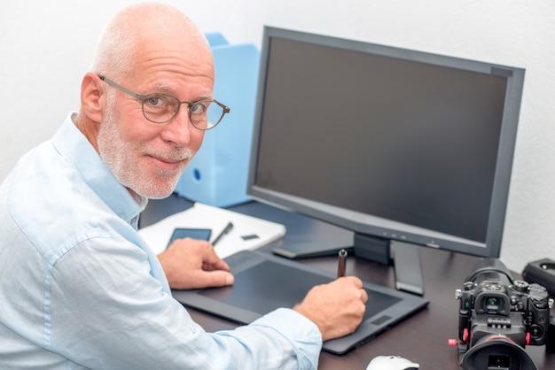 Dojrzały mężczyzna pracujący na jego tablet graficzny