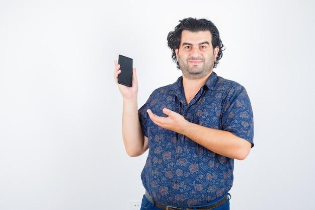 Dojrzały mężczyzna prezentuje telefon komórkowy w koszuli i wygląda pewnie. przedni widok.