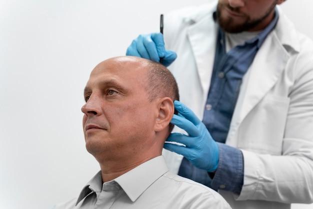 Dojrzały mężczyzna przechodzący proces ekstrakcji jednostek pęcherzykowych