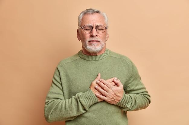 Dojrzały mężczyzna przyciska ręce do serca ma problemy z kardio, cierpi na zawał serca i ból w klatce piersiowej stoi z zamkniętymi oczami, potrzebuje pomocy lekarzy, nosi zwykły sweter odizolowany na brązowej ścianie