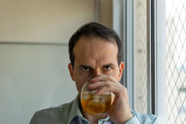 Dojrzały mężczyzna relaksujący się przy whisky po długim dniu w pracy (zdjęcia w naturalnym świetle).