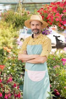 Dojrzały mężczyzna rolnik lub ogrodnik w fartuch i kapelusz stojący w szklarni wśród kwietników i kwiatów doniczkowych