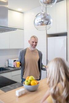 Dojrzały mężczyzna rozmawia z córką w kuchni