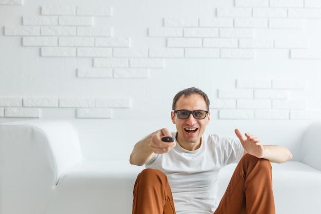 Dojrzały mężczyzna siedzi na kanapie przed telewizorem