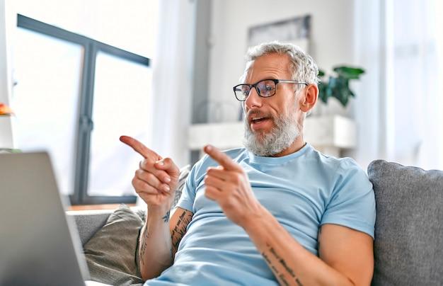 Dojrzały mężczyzna siedzi w domu na kanapie z laptopem na kolanach i rozmawia przez wideo.