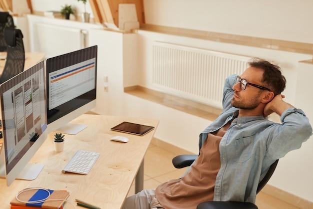 Dojrzały mężczyzna siedzi w miejscu pracy i patrząc na monitory komputerowe on pracuje nad oprogramowaniem w biurze