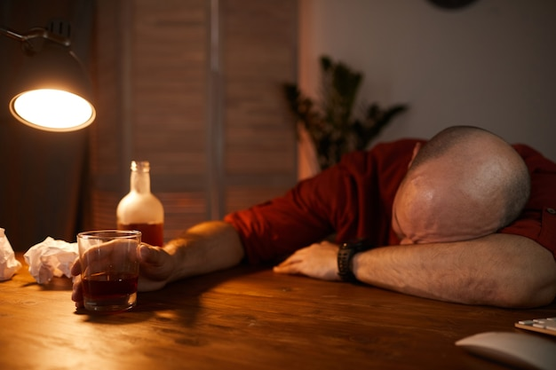 Dojrzały mężczyzna śpi przy stole po wypiciu napojów alkoholowych podczas imprezy