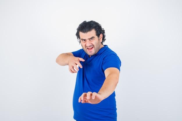 Dojrzały mężczyzna stojący prosto, pozując w niebieskiej koszulce, dżinsach i patrząc zły. przedni widok.