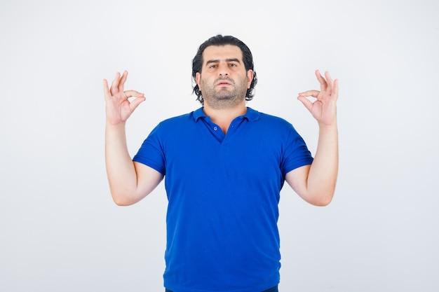 Dojrzały mężczyzna stojący w pozie medytacji w niebieski t-shirt, dżinsy i wyglądający na zrelaksowanego