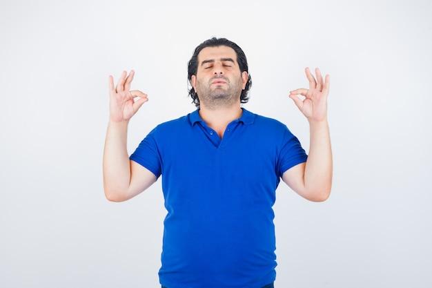 Dojrzały mężczyzna stojący w pozie medytacji w niebieskiej koszulce, dżinsach i patrząc zrelaksowany, widok z przodu.