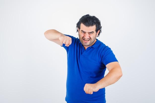 Dojrzały mężczyzna stojący w pozie walki w niebieskiej koszulce, dżinsach i patrząc pewnie. przedni widok.