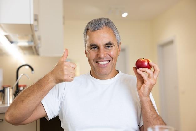 Dojrzały mężczyzna trzyma czerwone, świeże jabłko, kciuki w górę i uśmiechy