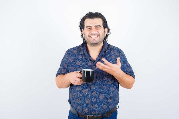 Dojrzały mężczyzna trzyma kubek w koszuli i wygląda zachwycony. przedni widok.
