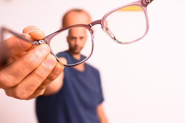 Dojrzały mężczyzna trzyma okulary astygmatyzmu z plastikowymi soczewkami polimerowymi