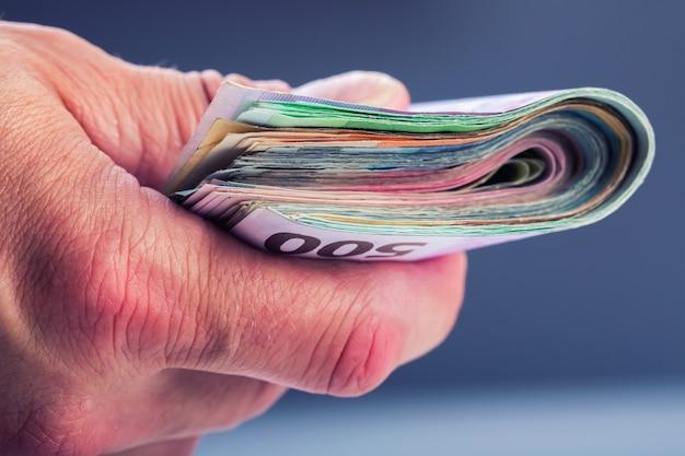 Dojrzały mężczyzna trzyma pakiet pieniędzy w palcach. banknoty waluty euro.