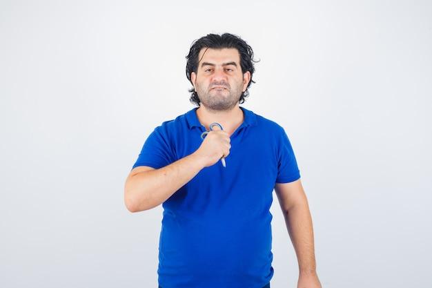 Dojrzały mężczyzna trzymając nożyczki, wydymając usta w niebieskiej koszulce i patrząc agresywnie, z przodu.