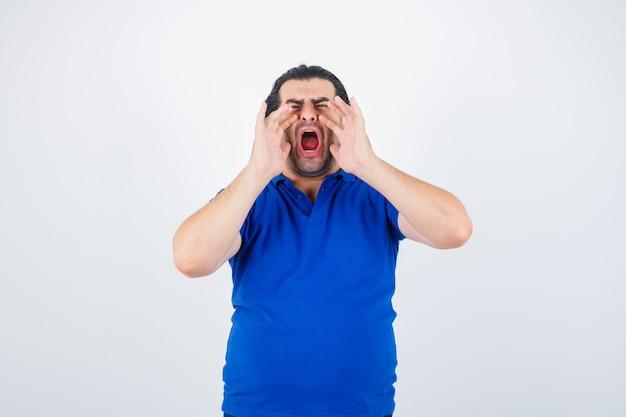 Dojrzały mężczyzna, trzymając się za ręce w pobliżu ust, dzwoniąc do kogoś w niebieskiej koszulce