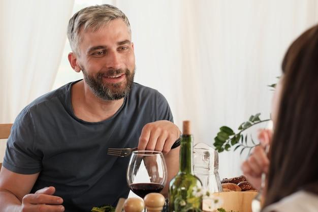 Dojrzały mężczyzna uśmiecha się do swojej kobiety, gdy siedzą przy stole i jedzą obiad w domu