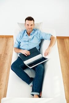 Dojrzały mężczyzna używa laptopa w domu