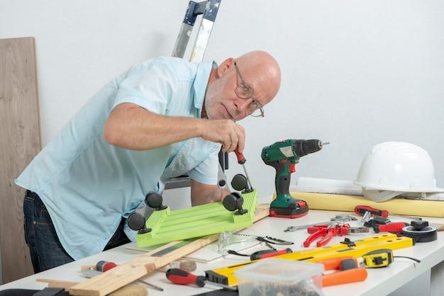 Dojrzały mężczyzna używa śrubokręt w domu