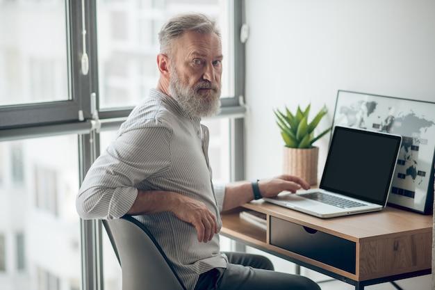 Dojrzały mężczyzna w białej koszulce pracujący na laptopie