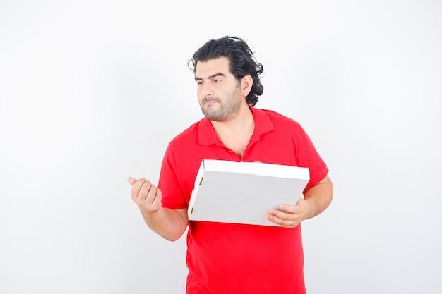 Dojrzały mężczyzna w czerwonej koszulce trzyma pudełko po pizzy, odwracając wzrok i patrząc zamyślony, widok z przodu.