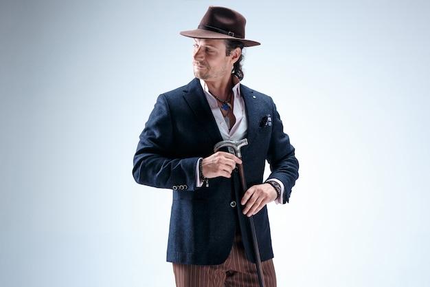 Dojrzały mężczyzna w garniturze i kapeluszu trzyma laskę. na białym tle na szarym studio.