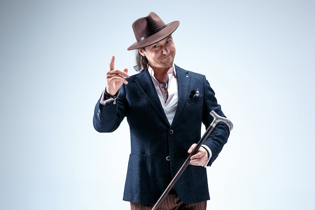 Dojrzały mężczyzna w garniturze i kapeluszu trzyma laskę. na białym tle na szarym tle studio.