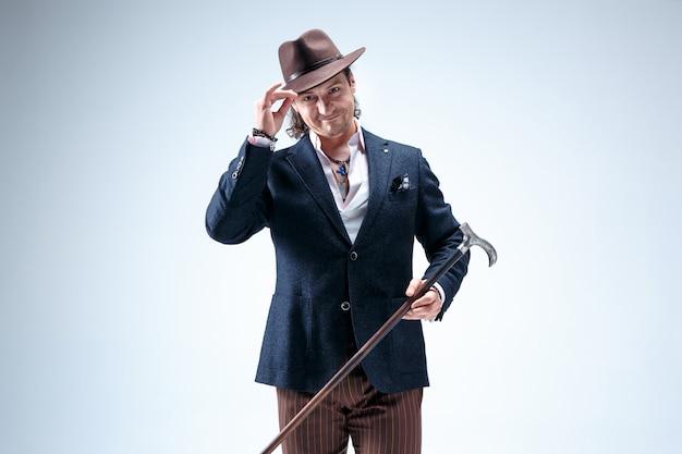 Dojrzały mężczyzna w garniturze i kapeluszu trzyma laskę. pojedynczo na szarym.