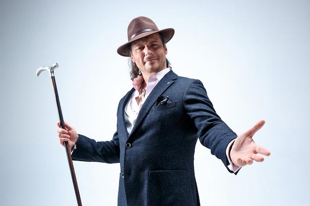 Dojrzały mężczyzna w garniturze i kapeluszu trzyma laskę.