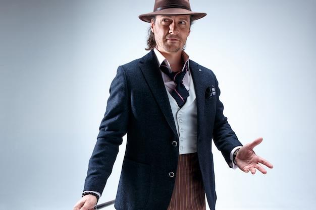 Dojrzały mężczyzna w garniturze i kapeluszu trzymającym laskę.