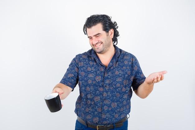 Dojrzały mężczyzna w koszuli, trzymając kubek i patrząc szczęśliwy, widok z przodu.