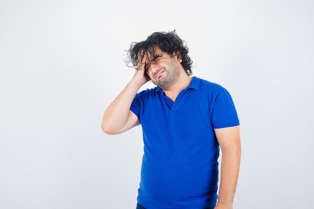 Dojrzały mężczyzna w niebieskiej koszulce cierpi na silny ból głowy i wygląda na zirytowanego, widok z przodu.