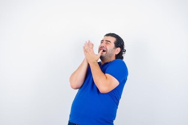 Dojrzały mężczyzna w niebieskiej koszulce, dżinsy, podnosząc ręce w przestraszony sposób i wyglądający na przestraszonego, widok z przodu.