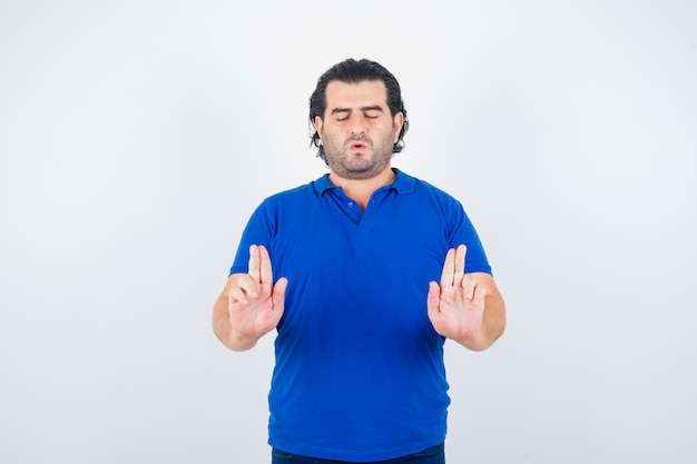 Dojrzały mężczyzna w niebieskiej koszulce, dżinsy pokazujące gest pieniędzy i wyglądający spokojnie, widok z przodu.