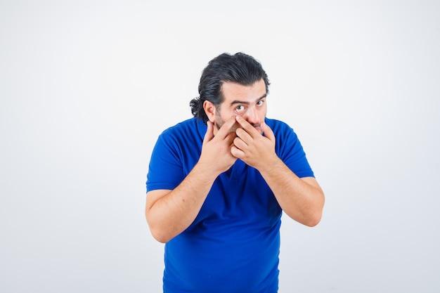Dojrzały mężczyzna w niebieskiej koszulce, dżinsy, ściągając powiekę i patrząc poważnie, widok z przodu.