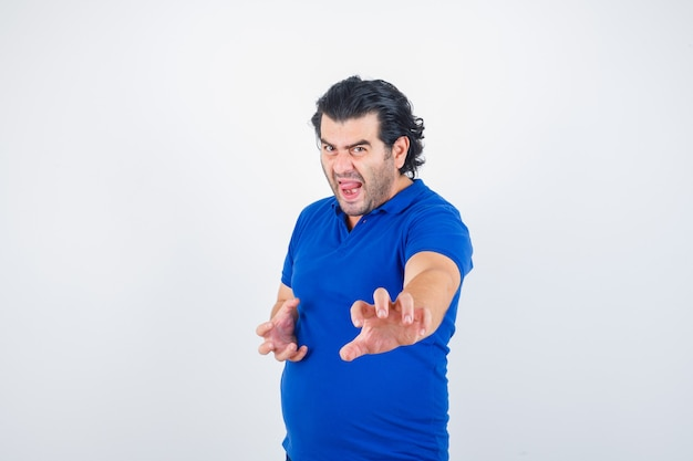 Dojrzały mężczyzna w niebieskiej koszulce, stojący w pozie walki i patrząc zły, widok z przodu.