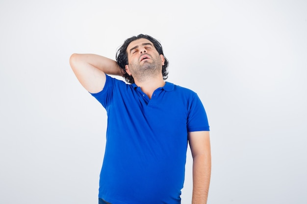 Dojrzały mężczyzna w niebieskiej koszulce, trzymając rękę za głową i patrząc senny, widok z przodu.