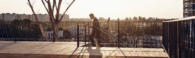 Dojrzały mężczyzna w pełnym garniturze wchodzi po schodach z zachodem słońca w tle