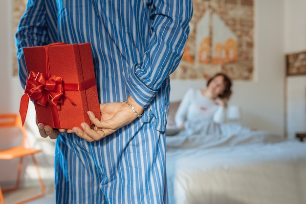 Dojrzały mężczyzna w piżamie, podając niespodziankę na walentynki, aby jej żona zrelaksowała się w domu w łóżku