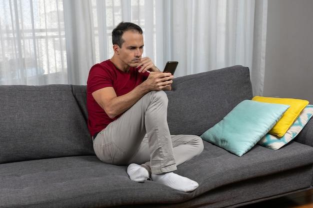 Dojrzały mężczyzna w wieku lat siedzi na kanapie w skarpetkach i bawi się smartfonem.