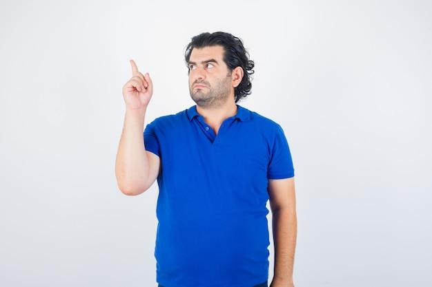 Dojrzały mężczyzna wskazujący w lewo z palcem wskazującym w niebieskiej koszulce, dżinsach i patrząc skoncentrowany. przedni widok.