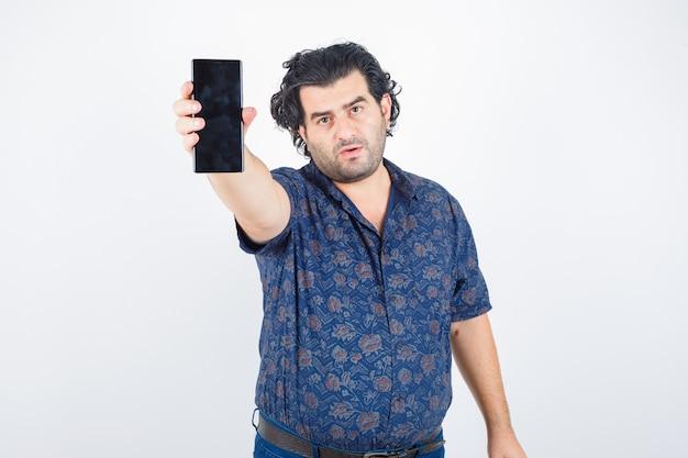 Dojrzały mężczyzna wyciąga rękę, aby pokazać telefon komórkowy w koszuli i wygląda pewnie. przedni widok.