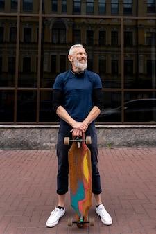 Dojrzały mężczyzna z deskorolką zrównoważoną mobilność