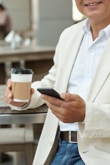 Dojrzały mężczyzna z gadżetem w kawiarni ulicznej