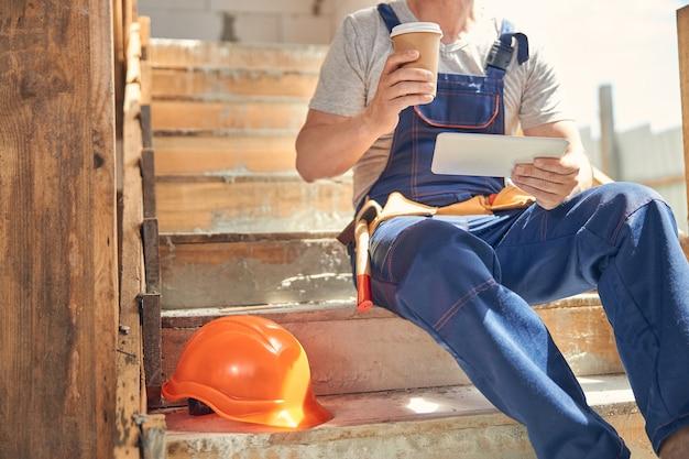 Dojrzały mężczyzna z komputerem typu tablet siedzący na schodach
