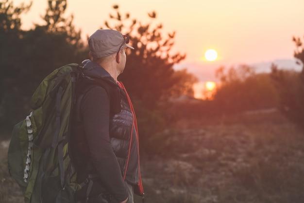 Dojrzały mężczyzna z plecakiem w czapce patrzy na zachód słońca w lesie