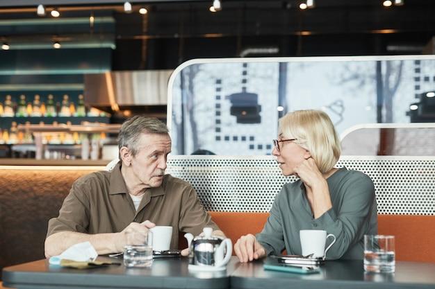 Dojrzały mężczyzna z wąsami siedzi przy stole i opowiada historię ciekawskiej dziewczynie podczas picia herbaty w kawiarni
