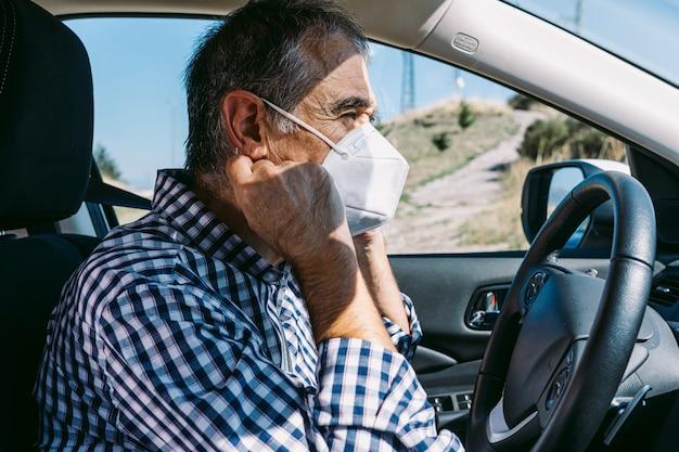 Dojrzały mężczyzna zakładający maskę w samochodzie, aby uchronić się przed covid-19