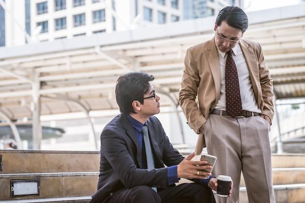 Dojrzały młody biznesmen używa cyfrową pastylkę dyskutować informację z starym biznesowego mężczyzna kolegą w nowożytnym biznesowym holu